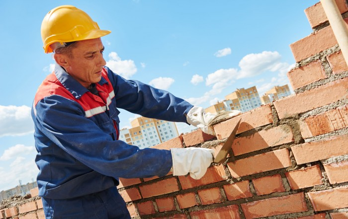 41576316 - construction worker. mason bricklayer installing red brick with trowel putty knife outdoors