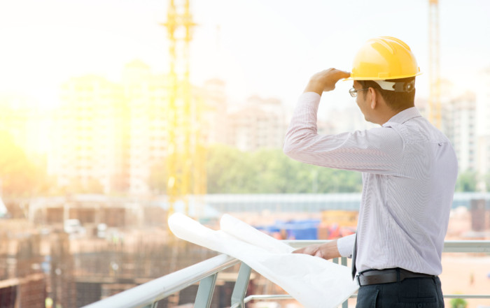 47875333 - asian indian male site contractor engineer with hard hat holding blue print paper looking away inspecting at construction site, crane with golden sunlight at the background.