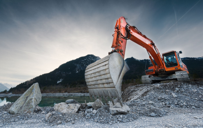 39092646 - heavy organge excavator with shovel standing on hill with rocks